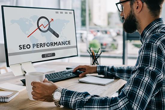 bearded man at computer performing seo analysis